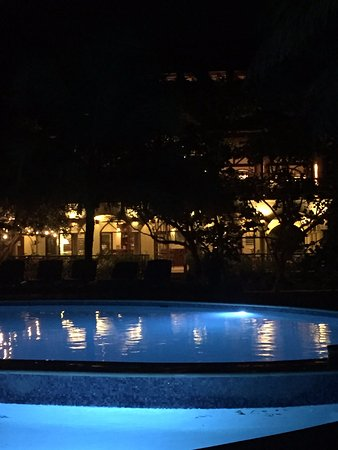 Hamanasi Adventure and Dive Resort: View of pool with main house in the background at night.