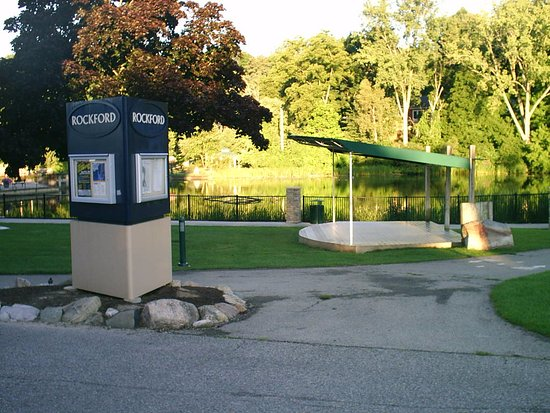 Rockford, MI: A city event kiosk is located close to the park's covered stage platform.