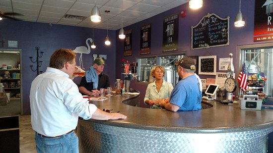 Corning, NY: The tasting room with friendly customers and windows looking into the brewing area.