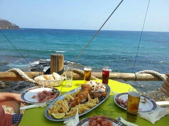 La Ola: Terraza con mesa sobre el mar.