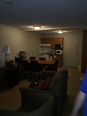 Hotel Motel Le Gite Inc.: living area, full table, kitchen area with fridge, microwave, sink and dishes
