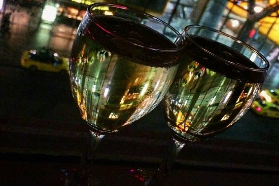 Vibe Savoy Hotel Melbourne: A glass of sparkling and a view of Southern Cross at night.