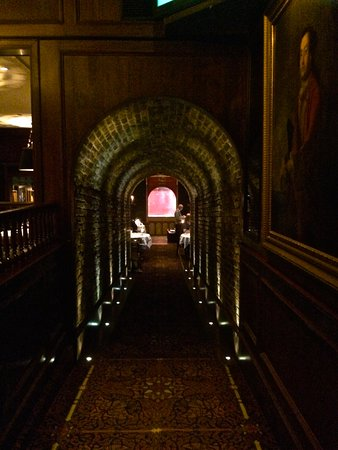 Hy's Steakhouse & Cocktail Bar: Entrance tunnel to dining room downstairs - they grill meat behind the glass at end.