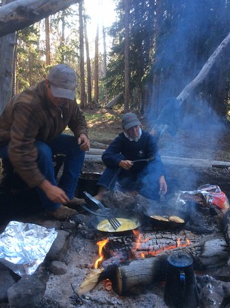 Dubois, WY: Guide and wrangler cook breakfast over the campfire.