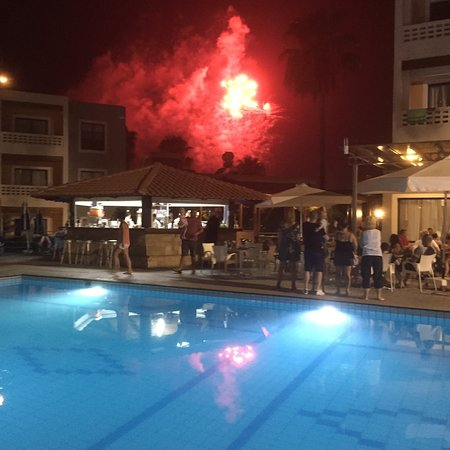 Damon Hotel Apartments: a view of the pool bar at night fireworks from another hotel