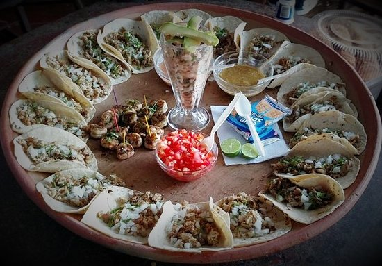 "Poneloya, Nicaragua: ""A lil' bit of everything"" plate. Comes with 10 carnitas (pork) tacos, Mexican ceviche & garlic"