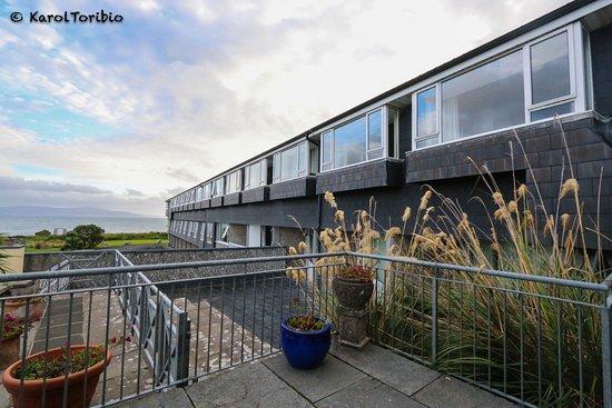 Furbo, أيرلندا: Zona exterior trasera del hotel con vistas al mar, 1ª terraza blanca de la dcha nuestra habitaci