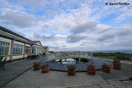 Furbo, أيرلندا: Zona exterior trasera del hotel con vistas al mar, estanque