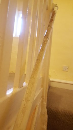 Newton Poppleford, UK: main stairwell rail caked in dirt (yes some of it is rust/ flaked paint) but mainly dirt