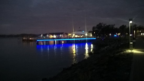 """Alongside"" restaurant lit up, reflecting on the water, Paihia."