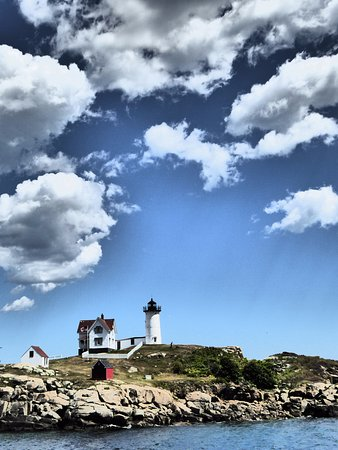 Cape Neddick Nubble Lighthouse: Nubble lighthouse with fluffy clouds