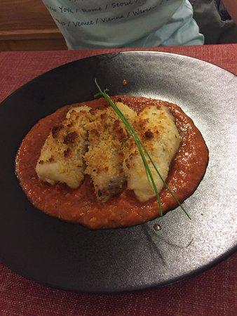 Fisch und Spaghetti eingerollt und mit Käse überbacken auf schwarzem Teller