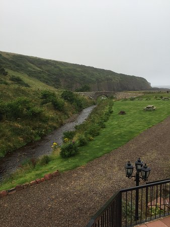 Pennan, UK: the romantic stream and old bridge that runs to the ocean