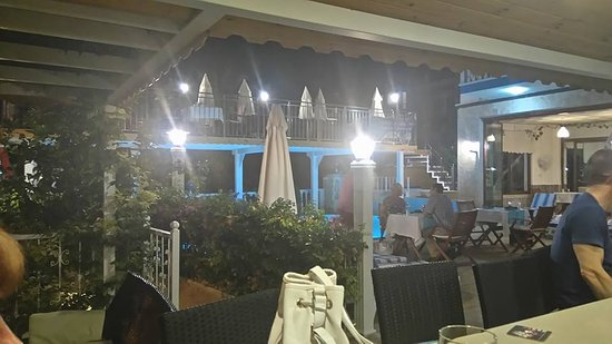 Kelebek Hotel: View from the bar across the poolside set for evening meals, with the raised area at the rear