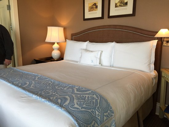 The Ocean House: Bedroom of Oceanfront Suite. The pillow's initial is for the guest's surname