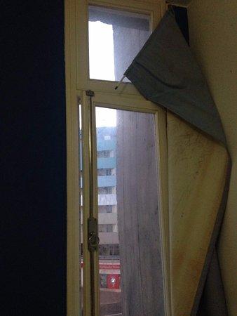 Hotel Gorgulho: rideau au dessus du lit sale et cassé, impossible à rattacher, vitre non lavée