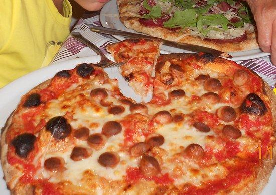 """Province of Bari, Italie : in primo piano pizza e wurstel dietro """"pizza"""" bresaola rucola e grana"""