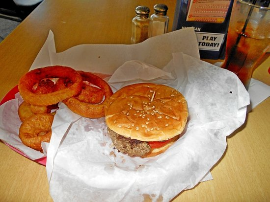 Hamburger with flat bread bun and onion rings.