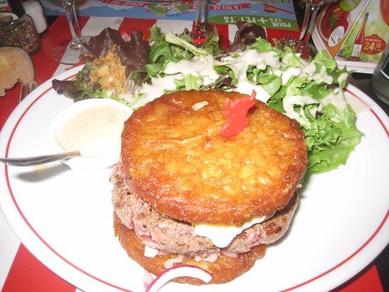 Restaurant la Boucherie : le steack hâché servi entre 2 galettes de pommes de terre avec sauce fromage, bacon et oignon.