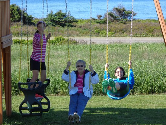 Cavendish Beach Cottages: swingset -- fun for young and old alike (This woman is 85!)