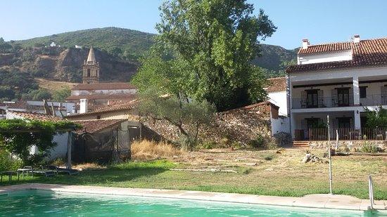 Alájar, España: Desde la piscina se ven las habitaciones a la derecha y al fondo la torre de la iglesia y la Peñ