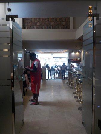 Hellinis Hotel: Entrada para o bar (logo de ingressar) e sala com mesas para o café-da-manhã e sofás para os hós