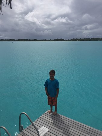 ‪منتجع The St. Regis Bora Bora Resort: My son standing on the edge of the deck of our bungalow. The water was about 8' deep, and beauti‬