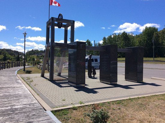 Elliot Lake, Canada: An actual shivel wheel and 3 granite columns that have history and stats of mines in the area