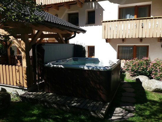 Almhotel Bergerhof: vasca idromassaggio nel giardino posteriore