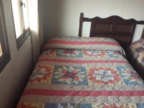 Hotel Villa Espanola: Una de las camas a la par de la ventana, espacio reducido entre una y otra.