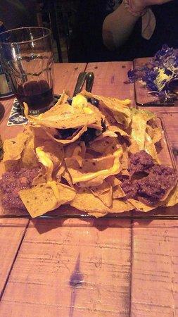 Nachos con frijoles, carne, guacamole y queso cheddar