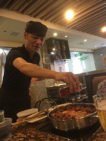 HuangJiHuang Three-Sauce Simmer Pot : Waiter adding fresh cilantro to simmering pan