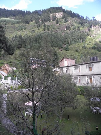 Honeymoon Inn Manali: Uitzicht vanuit onze kamer, aan de achterzijde: mooie bergen, appelbomen en de tuin met zitjes.