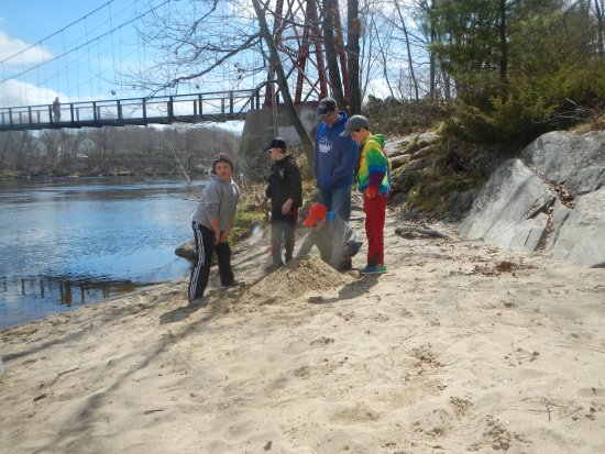 Androscoggin Brunswick-Topsham Riverwalk : Playing on a beach with the swinging bridge in background.