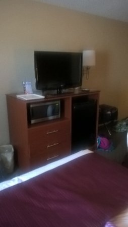 Quality Inn : TV Stand with microwave and fridge in room.