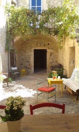 Mirmande, Frankreich: Le café Patine se trouve à droite après le banc ...