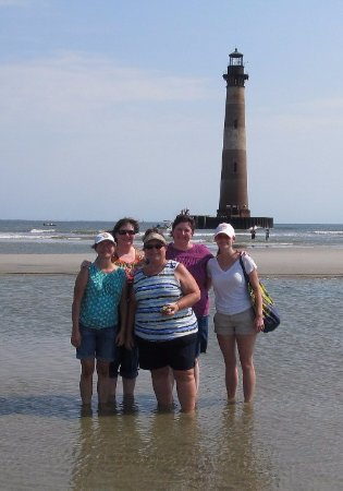 Folly Beach, SC: Us Gals on the sandbar with Morris Island Lighthouse in background.
