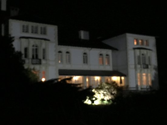 Lampeter, UK: The Falcondale Hotel - panoramic view of the front of the hotel lit up after sunset