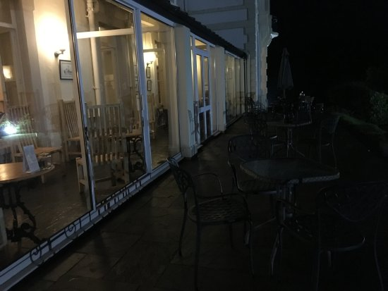 Lampeter, UK: The Falcondale Hotel - view of the terrace and conservatory (front of the hotel) lit up after su