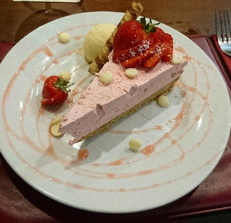 Ammanford, UK: Strawberry and white chocolate chip cheesecake with a minted strawberry syrup.