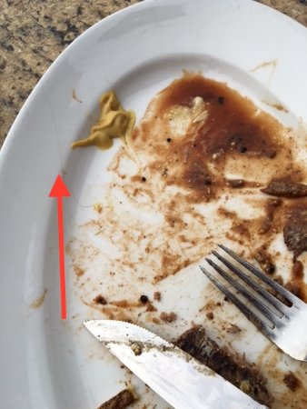 Mon Ami Gabi: The piece of black hair on my Steak dish which it was over cooked