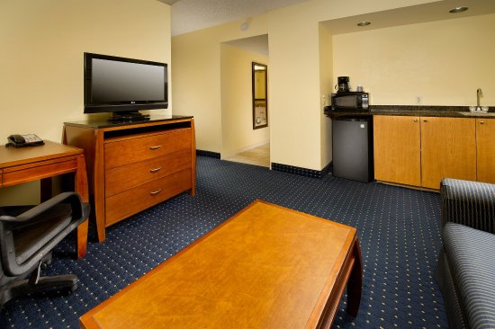 Holiday Inn Express Miami Airport Doral: Suite Living Area with mini-fridge, sofa, and flat screen TV