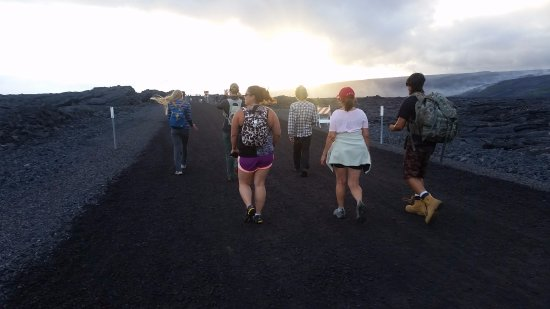 Pahoa, HI: Part 1 = Walk on gravel road to see the lava flowing into the Ocean. Notice our guide's backpack