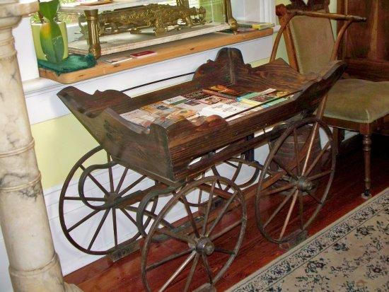 The Parisian Courtyard Inn: Entry way with a quaint antique buggy holding brochures.