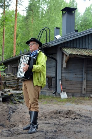 Kuopio, Finland: The smoke sauna in the background and the accordianist/folk singer in the foreground.
