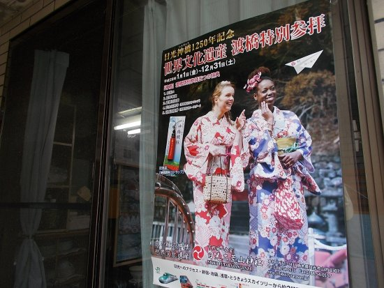 Shinkyo: A poster on a storefront along the long street to the start of the Heritage Area at the end