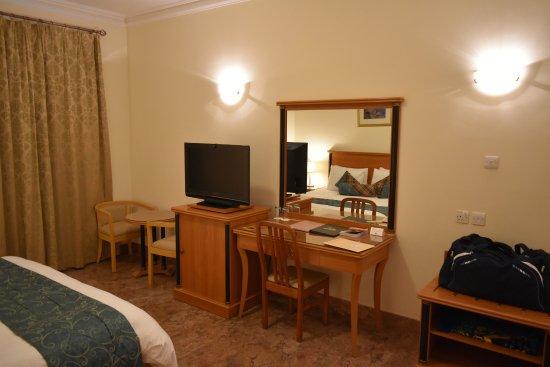 Falaj Daris Hotel: La chambre: espace bureau/TV/minibar.