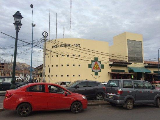 Avenida movimentada em frente ao Centro Artesanal Cusco