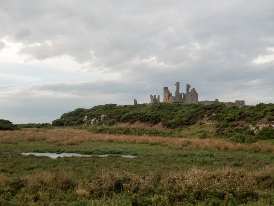 Craster, UK: A view of Dunstanburgh from across the marshy ground.