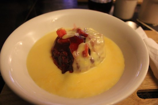 Повис, UK: Apple-blackberry crumble with custard - closeup